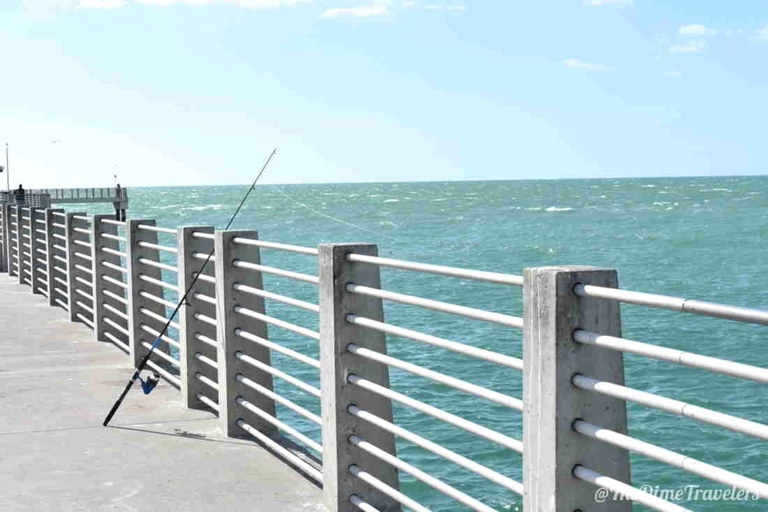 Fishing Pole leaning on pier by coean